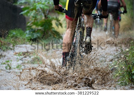 Mountain bikers driving in rain upstream creek - stock photo