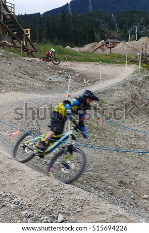 "Mountain bikers going down a winding course/  ""Racing to the Bottom"""
