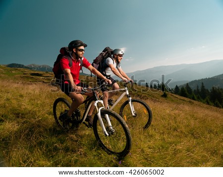 mountain bikers on a meadow, looking forward attentively at the beautiful landscape - stock photo