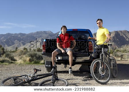 Mountain Bikers Waiting Behind a Truck - stock photo