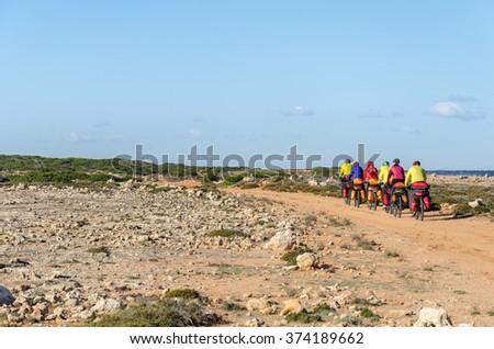 Mountain bikes rides along the winding dirt road along the sea - stock photo