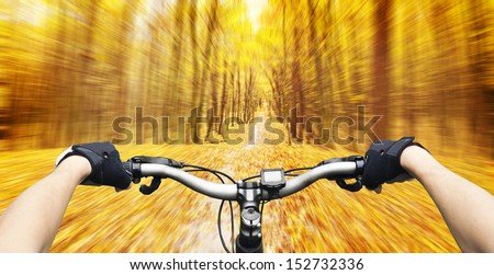 Mountain biking down hill descending fast on bicycle in autumn forest. View from bikers eyes.  - stock photo