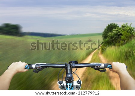 Mountain biking down hill descending fast on bicycle. View from bikers eyes - stock photo