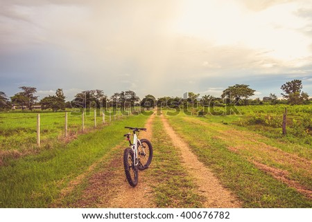 Mountain biking on single track beautiful nature green grass and cloud blue sky add vintage color filter - stock photo
