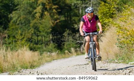 Mountain biking  - woman on bike - stock photo