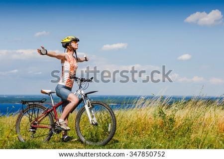 Mountain biking - woman with bike enjoy summer vacation - stock photo