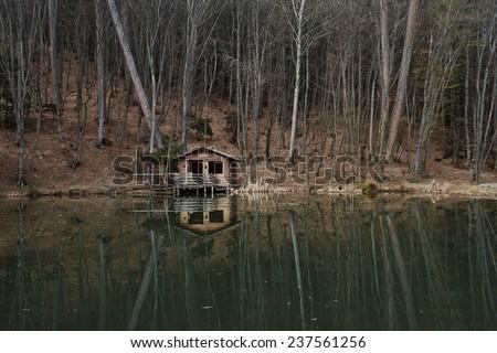 Mountain cabin in reflection - stock photo