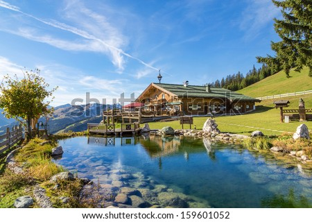 Mountain chalet with swimming pond - stock photo