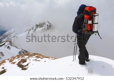 Mountain climber above clouds during winter