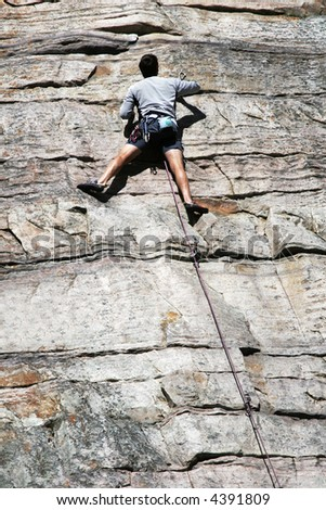 Mountain climber begins free ascent without any additional ropes to assist - stock photo