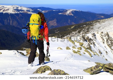 Mountain climber carries a backpack and climbing gear on snowy alpine route - stock photo