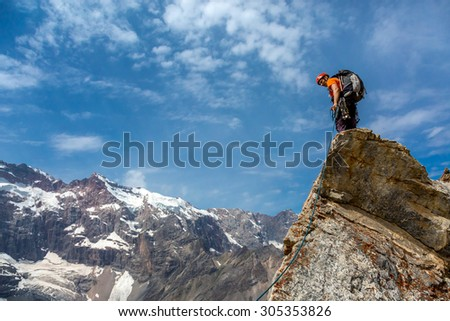Mountain climber on top. Rocky razor sharp pointed summit and silhouette of male climber staying on sky and remote high land ridge background daylight sunny day outdoors