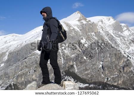 Mountain climber standing on peak - stock photo