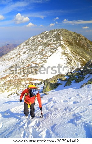 Mountain climber uses the ice axe while ascending a snowy slope - stock photo