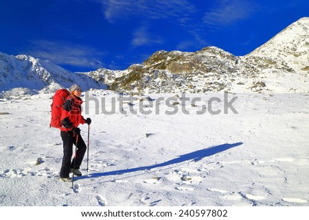 Mountain climbers ascending on snowy trail in fine winter day - stock photo