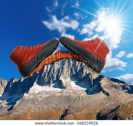 Mountain Climbing Concept / A pair of a mountaineering boots with a red climbing rope on a mountain peak with blue sky and sun rays - stock photo