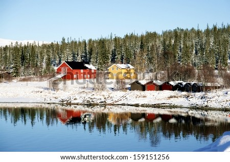 Mountain farm and boat houses by a lake in winter - stock photo