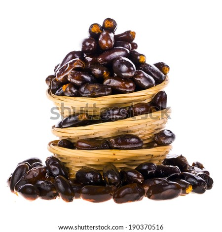 Mountain fresh dates, just in wicker baskets in a pile, isolated on white background. - stock photo