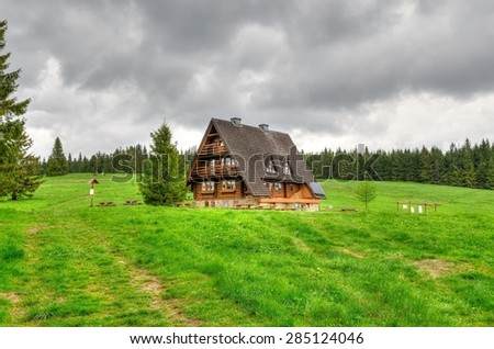Mountain hostel. View of wooden hut on the glade at the green wooded hill, Beskids mountains in spring season.