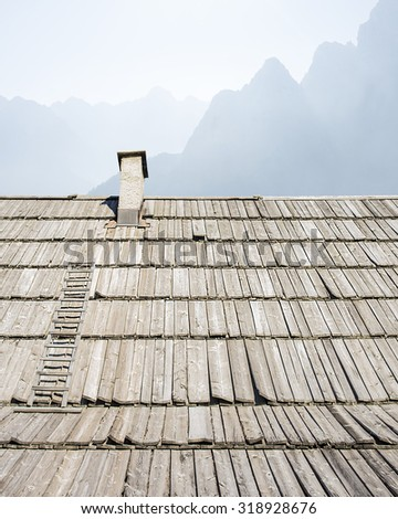 Mountain hut with a  background above the roof. - stock photo