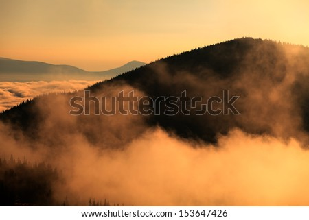 mountain in clouds and remote hills in morning fog, Carpathians landscape - stock photo