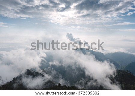 Mountain in the morning mist and surrounded by low clouds - stock photo