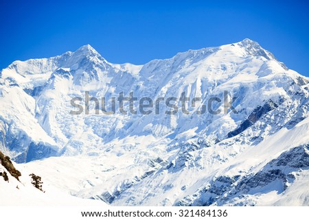 Mountain inspirational landscape in Himalayas, Annapurna range, Nepal. Mountain ridge with ice and snow over clear blue sunny sky. Annapurna 2 mountain peak 7937m.