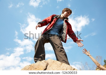mountain instructor handed someone a helping hand to the top of the mountain - stock photo