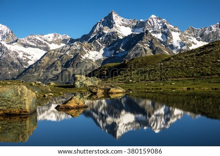 mountain lake in Switzerland near Matterhorn with reflection of the mountain peaks in water