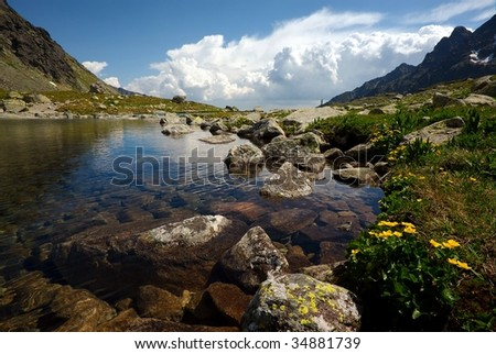 Mountain lake on plateau with a view under surface in sunny summer day with some clouds on horizon