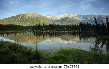 Mountain Lake Reflects Range in Background Alaska Wilderness North America USA - stock photo
