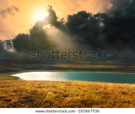 Mountain lake with dramatic clouds before the storm - stock photo