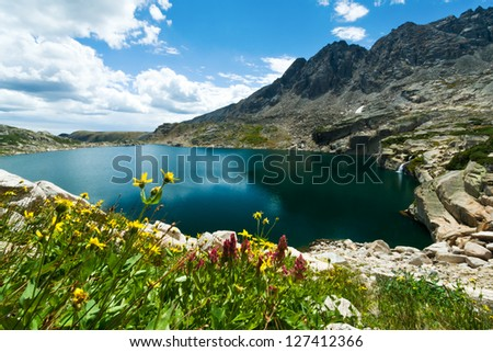 Mountain lake with waterfall and wildflowers blooming the Colorado summer - stock photo
