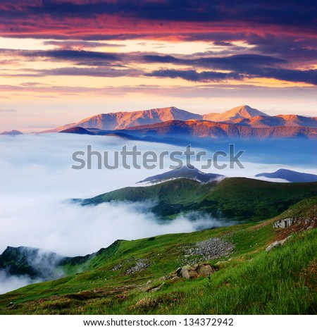 Mountain landscape. Beautiful morning with fog and the first rays of the sun - stock photo