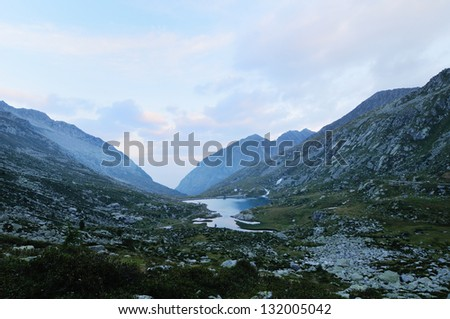 Mountain landscape before dawn (blue hour), with reservoir, meadows, rocks and clouds, cold cast