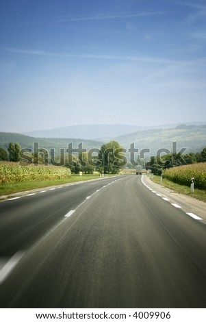 Mountain landscape - empty highway, clouds and the blue sky