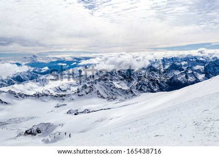 Mountain landscape in autumn or winter in Caucasus Mountains i Russia and Georgia. View from slopes of Mount Elbrus 5642m. Lot of white snow on rocky mountain ridge over blue sunny sky, Russia. - stock photo