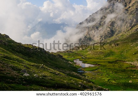 Mountain landscape in green valley with small lake and colouds, Caucasian mountains. - stock photo