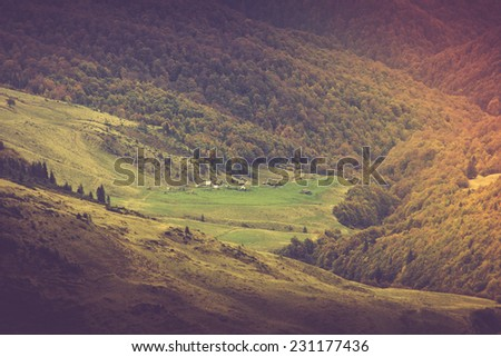 Mountain landscape of  village in warm autumn rays.Filtered image:cross processed vintage effect.