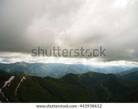Mountain landscape. The road in the mountains covered by forest. Light rays pierces way through the gloomy low clouds. Caucasus Mountains. - stock photo