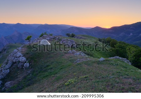 Mountain landscape with a beautiful sunset. Camping in the outdoors with a tent - stock photo