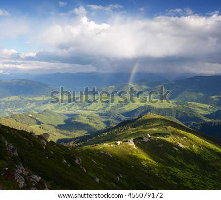Mountain landscape with a rainbow. Sunny summer day with blue skies and beautiful cumulus clouds - stock photo