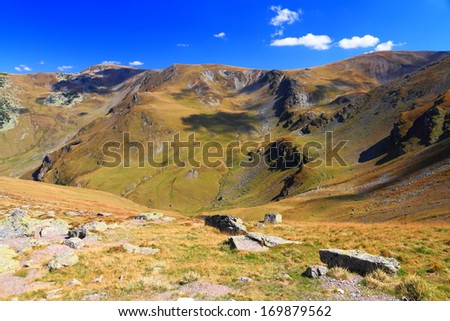 Mountain landscape with deep valley and distant summits in autumn - stock photo