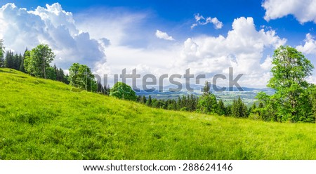 Mountain landscape with meadow in the foreground against a background of mountain ranges and mountain villages
