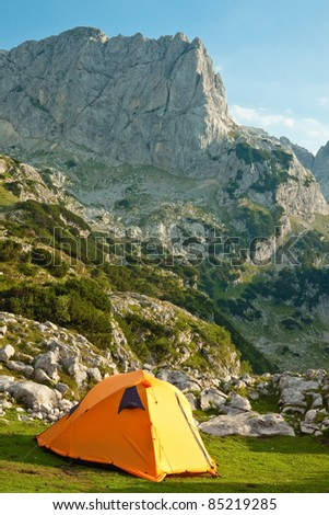 Mountain landscape with orange camping tent. National park Durmitor, Montenegro - stock photo