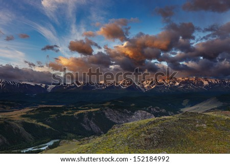 Mountain landscape with river and snowy peaks at sunrise - stock photo