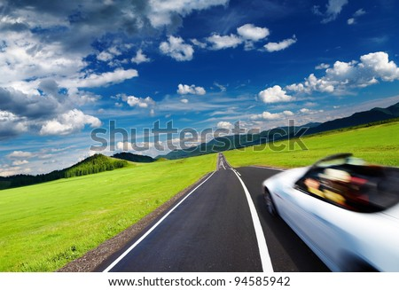 Mountain landscape with road and moving car - stock photo