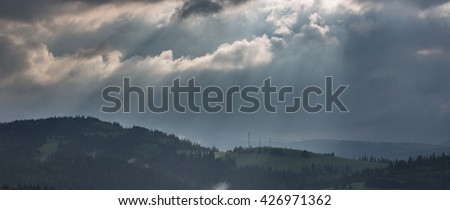 Mountain landscape with storm clouds at dawn in the rain - stock photo