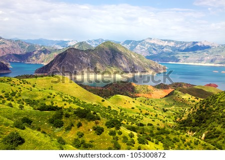 Mountain morraine lake and green rocks under blue sky - stock photo