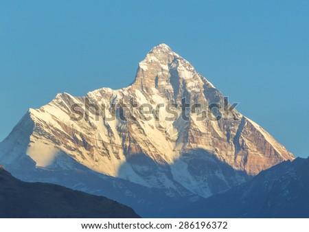 mountain Nanda Devi peak in Uttrakhand, India as seen during suset - stock photo